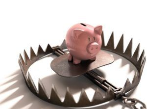 Piggy bank in the bear trap on white background.